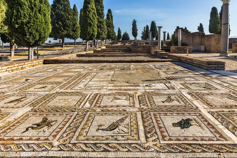 day trips from seville, italica with a roman mosaic in blue sky