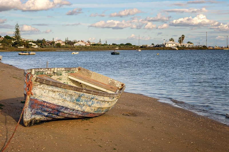 VIew of old wooden boat ashore in the beach of El Rompido, Huelva, Spain.