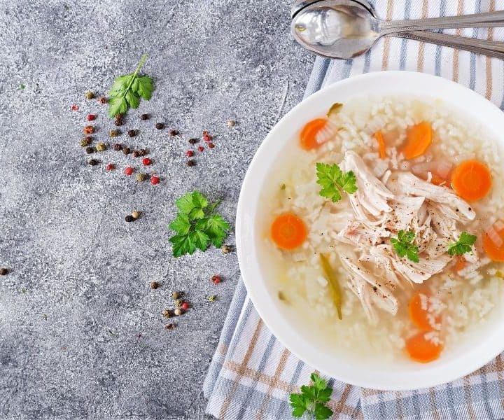 Dietary chicken soup with rice and carrots. Healthy food. Flat lay. Top view